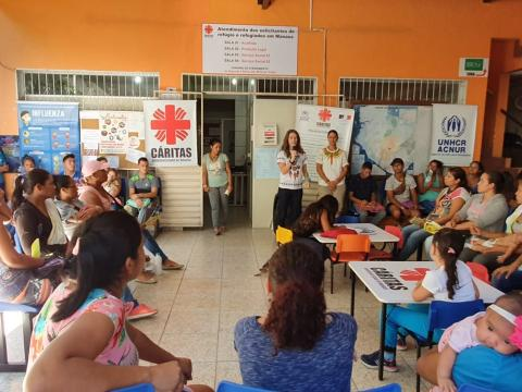 Sr. Roselei Bertoldo holds the microphone and speaks to a group a women about sexual abuse, exploitation, and human trafficking