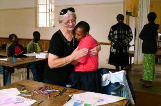 Maryknoll Sister Mary Frances Kobets (left) hugs a student in Zimbabwe