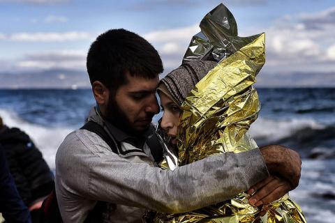 Refugees and migrants arrive at the Greek island of Lesbos after crossing the Aegean sea from Turkey on September 30, 2015