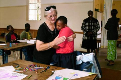 Maryknoll Sister Mary Frances Kobets (left) hugs a student in Zimbabwe
