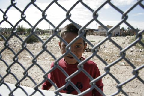 Boy on Mexican side of the border fence in El Paso